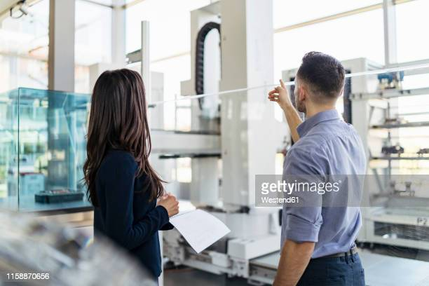 rear view of businessman and businesswoman talking in modern factory - finanzen und wirtschaft stock-fotos und bilder
