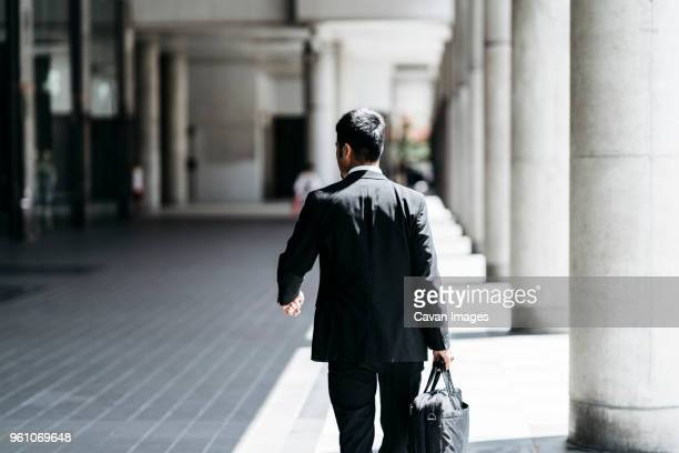 rear view of businessman carrying briefcase while walking at colonnade - 後ろ姿 ストックフォトと画像