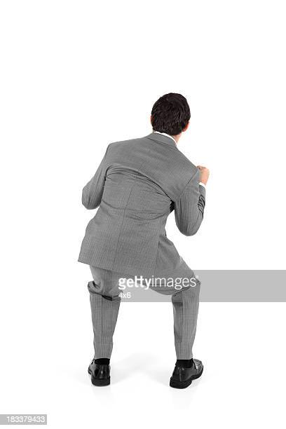 rear view of businessman crouching - crouching stock pictures, royalty-free photos & images
