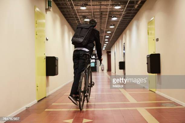 Rear view of businessman cycling in corridor
