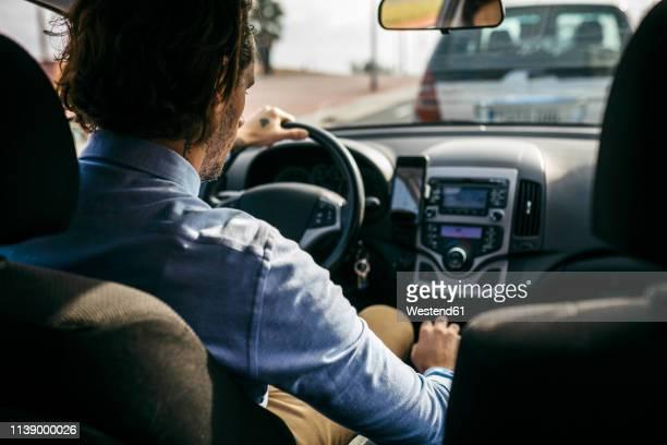 rear view of businessman driving car - motorista ocupação imagens e fotografias de stock