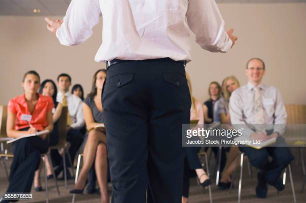 Rear view of businessman giving presentation to audience