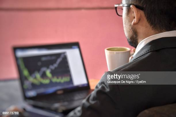 Rear View Of Businessman Having Coffee While Working On Laptop In Office