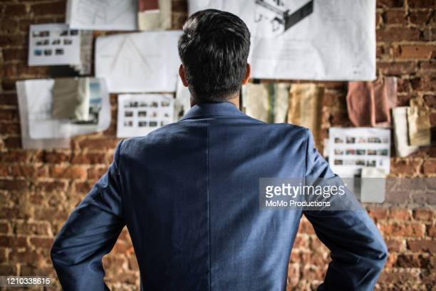 rear view of businessman looking at creative wall - 紺色 ストックフォトと画像