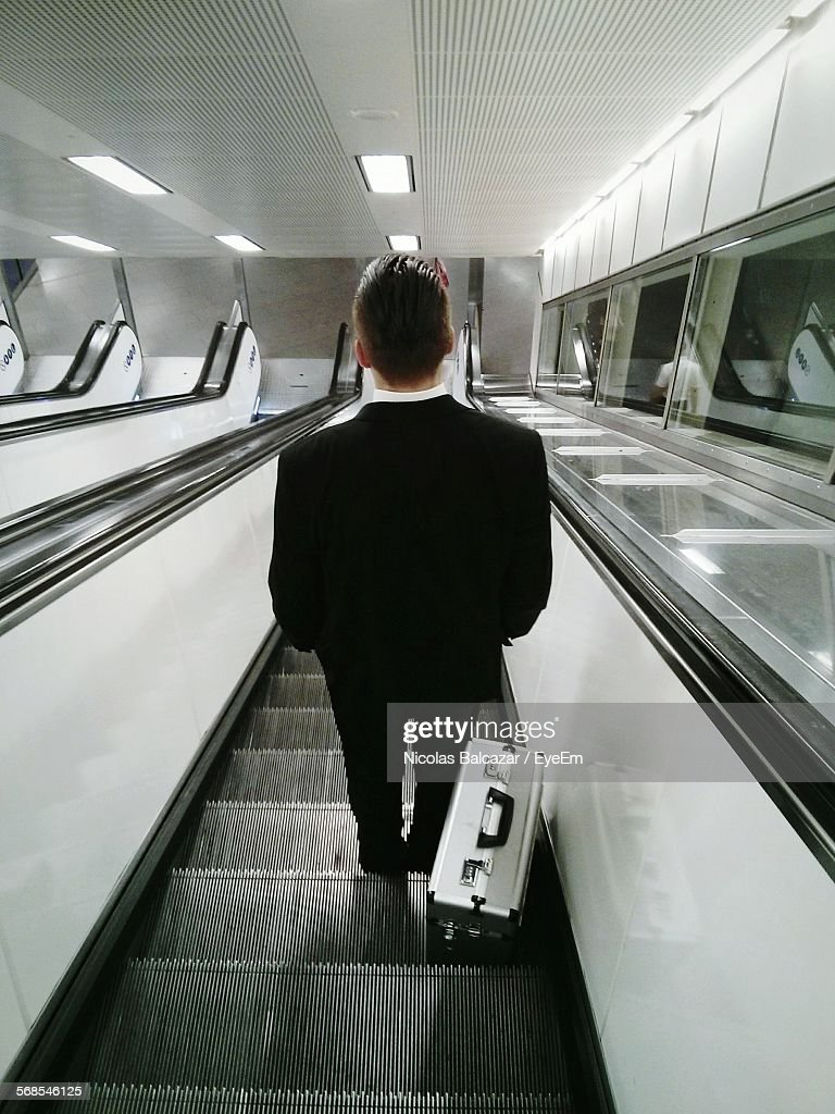 Rear View Of Businessman On Escalator Moving Down : Stock Photo