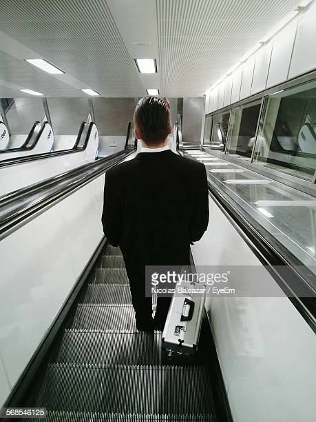 Rear View Of Businessman On Escalator Moving Down