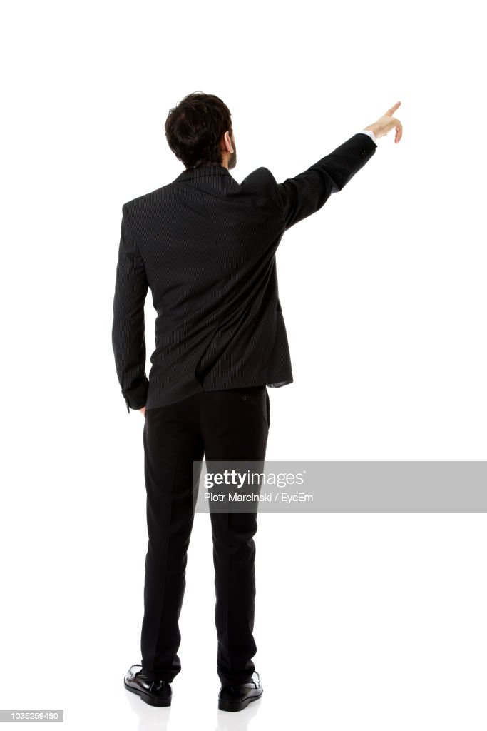 Rear View Of Businessman Pointing While Standing Against White Background : Stock Photo