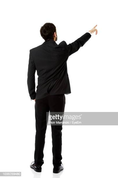 rear view of businessman pointing while standing against white background - apontando sinal manual - fotografias e filmes do acervo
