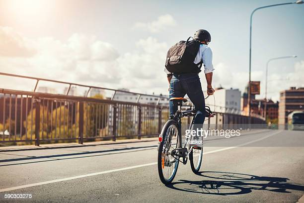rear view of businessman riding bicycle on bridge in city - sportschutzhelm stock-fotos und bilder