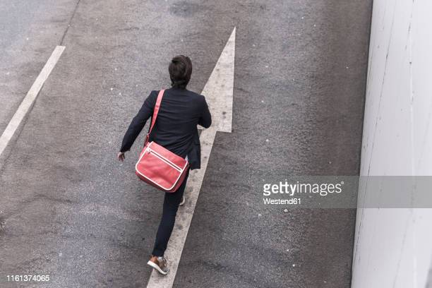 rear view of businessman running on road with arrow sign - runaway stock pictures, royalty-free photos & images