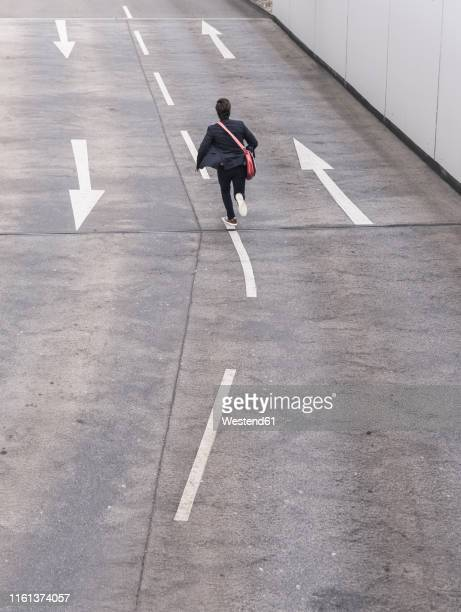 rear view of businessman running on road with arrow signs - runaway stock pictures, royalty-free photos & images