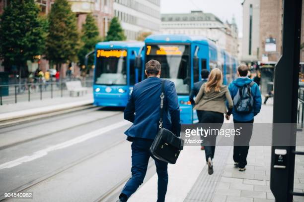 rear view of businessman running towards cable car on street in city - dringendheid stockfoto's en -beelden