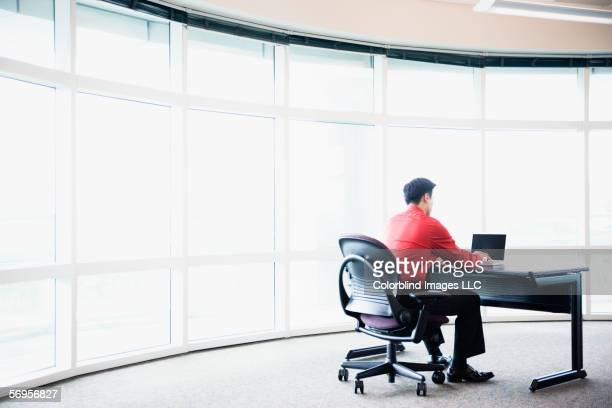 Rear view of businessman sitting at desk working on computer