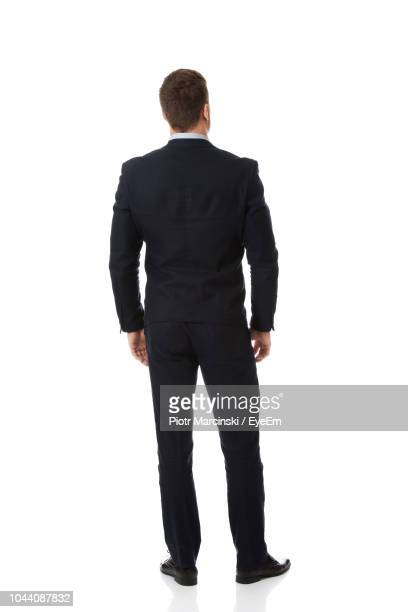 rear view of businessman standing against white background - anzug stock-fotos und bilder