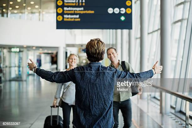 Rear view of businessman standing arms outstretched while greeting colleagues at airport