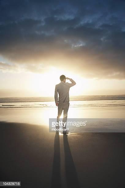 背面の眺め、ビーチの上に立つているビジネスマン