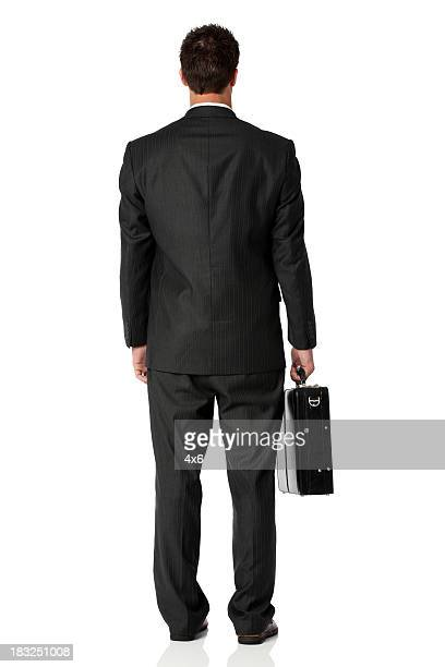 Rear view of businessman standing with briefcase