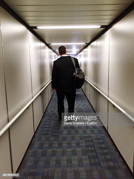 Rear View Of Businessman Walking In Passenger Boarding Bridge With Backpack