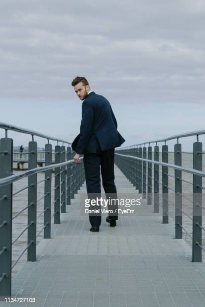 rear view of businessman walking on pier over sea against sky - 肩ごしに見る ストックフォトと画像