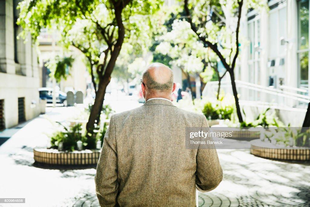 Rear view of businessman walking through building courtyard : Stock Photo