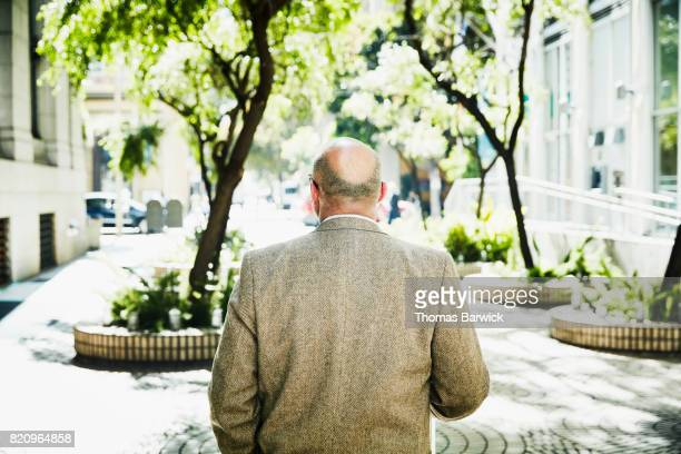 rear view of businessman walking through building courtyard - balding stock pictures, royalty-free photos & images