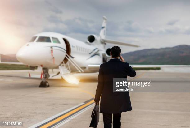 rear view of businessman walking towards private airplane - private aeroplane stock pictures, royalty-free photos & images