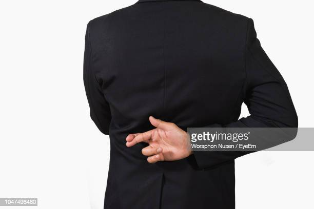 rear view of businessman with fingers crossed behind back while standing against white background - handen op de rug stockfoto's en -beelden