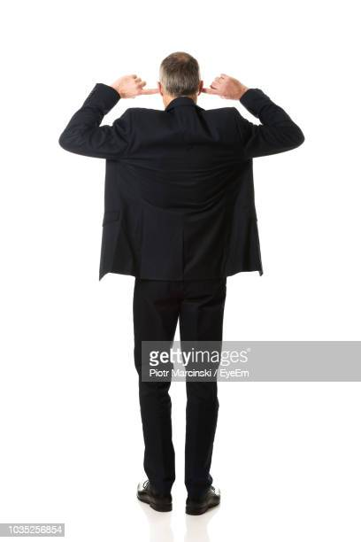 rear view of businessman with fingers in ears standing against white background - fingers in ears stock pictures, royalty-free photos & images
