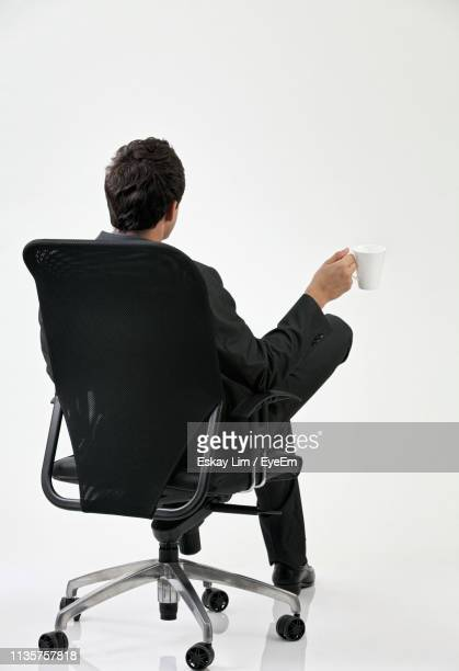 rear view of businessman with mug sitting on chair against white background - office chair stock pictures, royalty-free photos & images