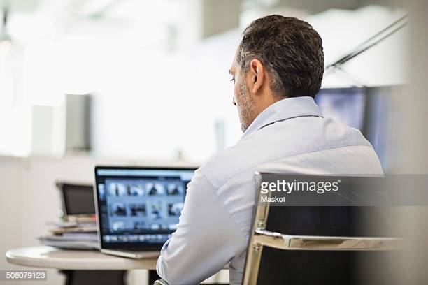 Rear view of businessman working at desk in office