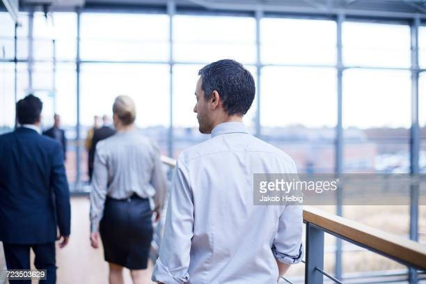 Rear view of businessmen and woman walking on office balcony