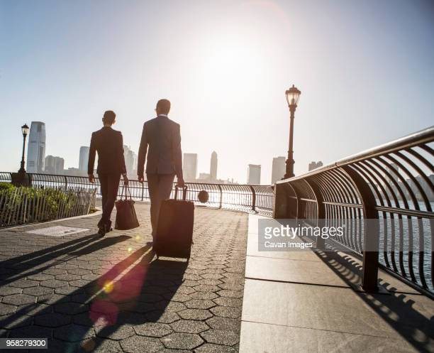 rear view of businessmen walking with luggage while walking on promenade during sunny day - gemeinsam gehen stock-fotos und bilder