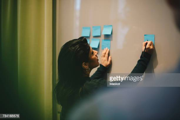 Rear view of businesswoman analyzing adhesive notes stuck on whiteboard in office