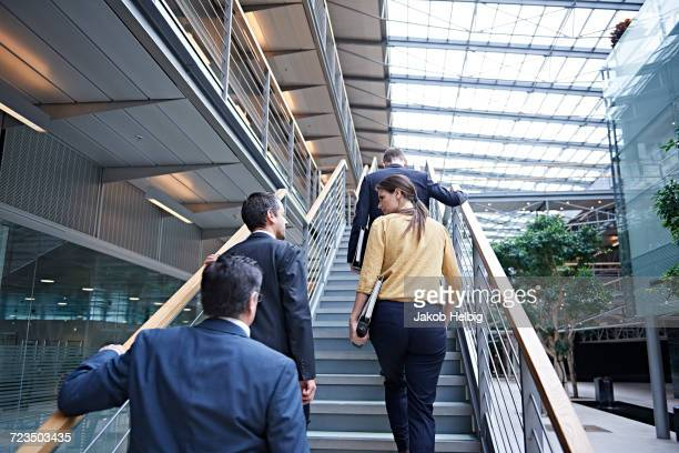 Rear view of businesswoman and men moving up office stairway
