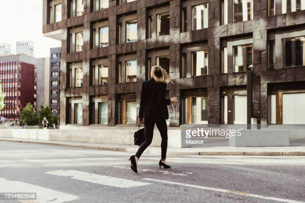 rear view of businesswoman crossing street against building - tenue soignée photos et images de collection