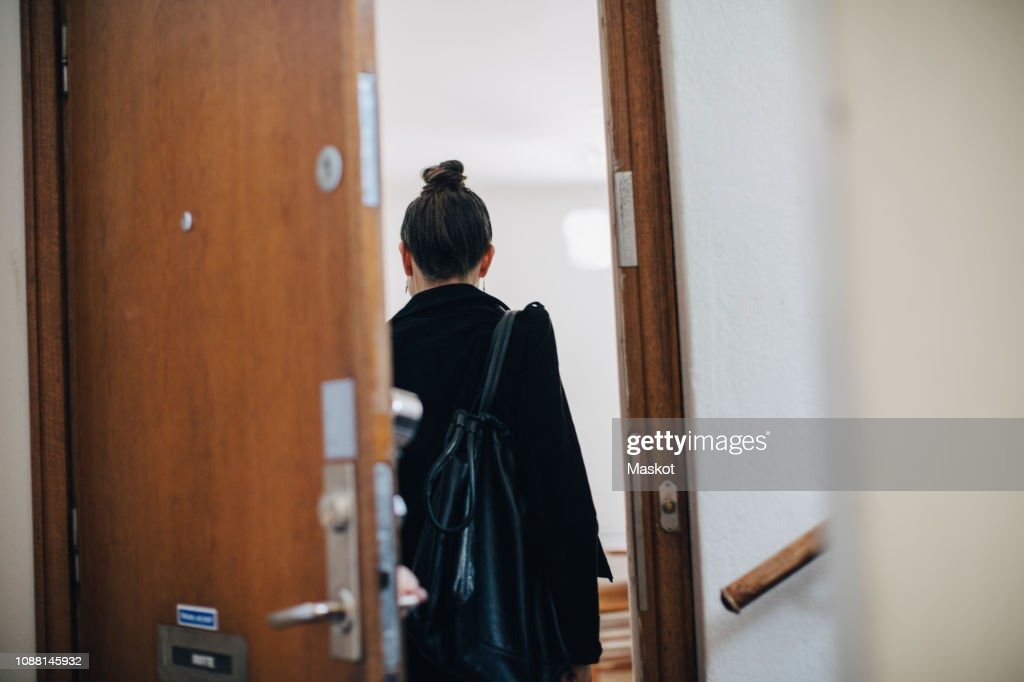 Rear view of businesswoman entering at coworker's apartment : Stock Photo