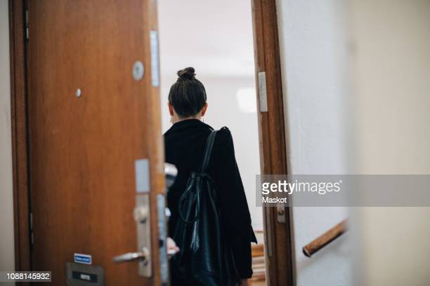 rear view of businesswoman entering at coworker's apartment - ankunft stock-fotos und bilder