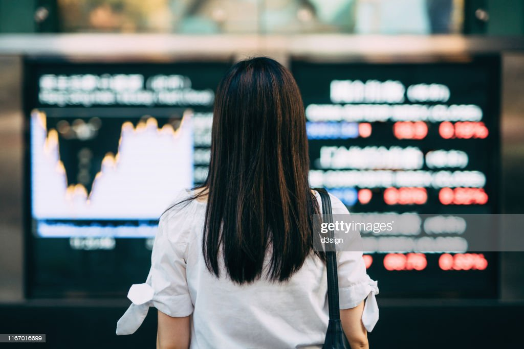 Rear view of businesswoman looking at stock exchange market display screen board in downtown financial district : Stock-Foto