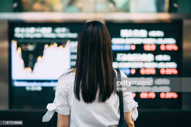 rear view of businesswoman looking at stock exchange market display screen board in downtown financial district - economia fotografías e imágenes de stock