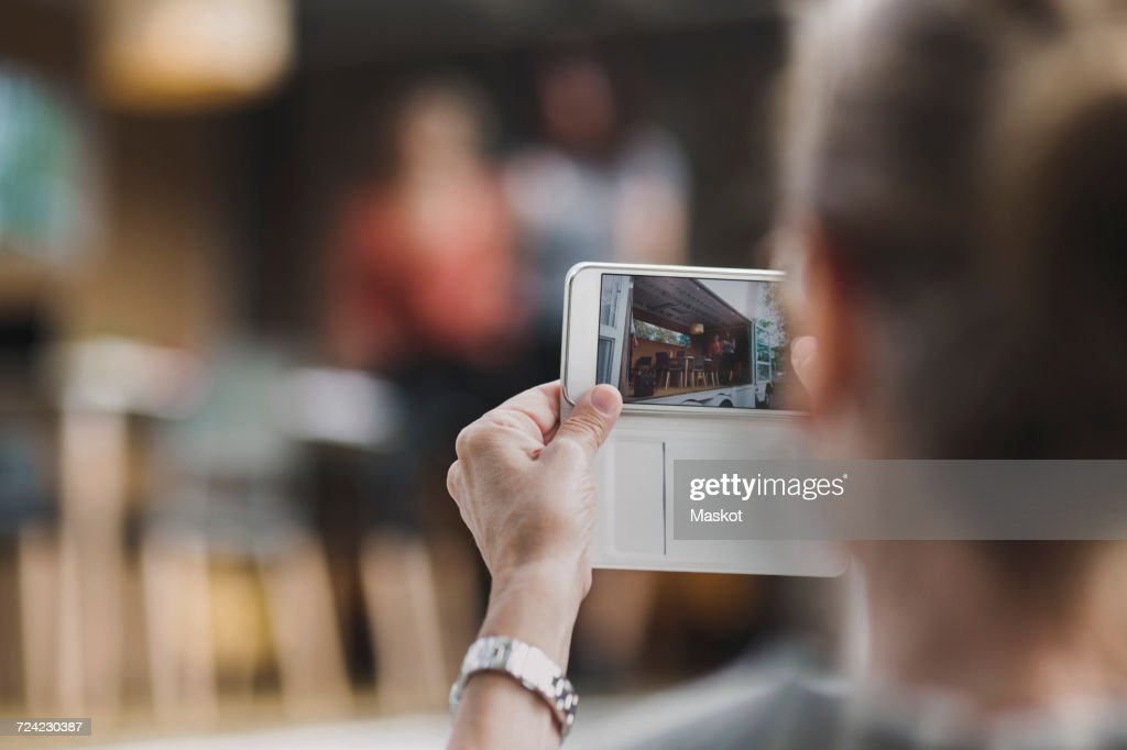 Rear view of businesswoman photographing colleagues through mobile phone in portable office truck : Stock Photo