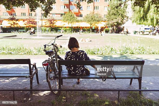 Rear view of businesswoman sitting on park bench by bicycle