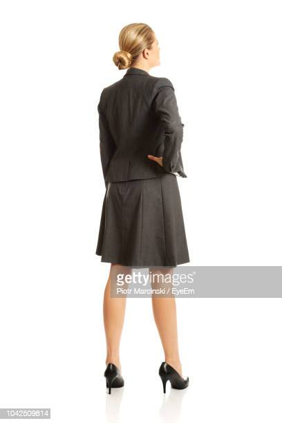 rear view of businesswoman standing against white background - op de rug gezien stockfoto's en -beelden