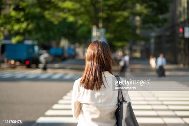 交通信号を待っているビジネスウーマンの背面図 - 待つ ストックフォトと画像