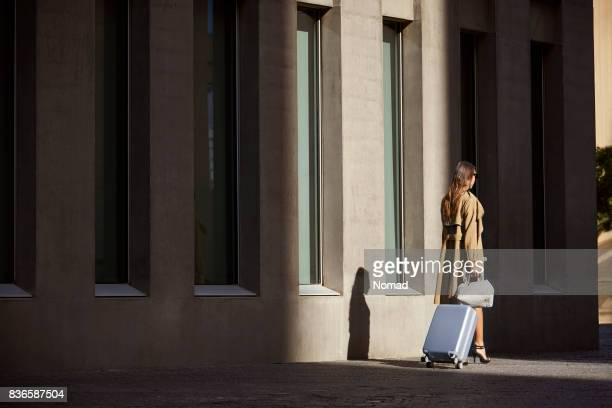 Rear view of businesswoman walking by airport