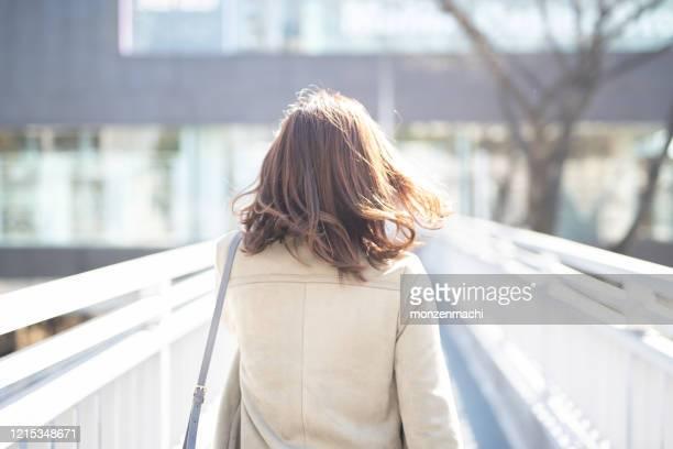 歩道橋を歩くビジネスウーマンの背面図 - 後ろ姿 ストックフォトと画像