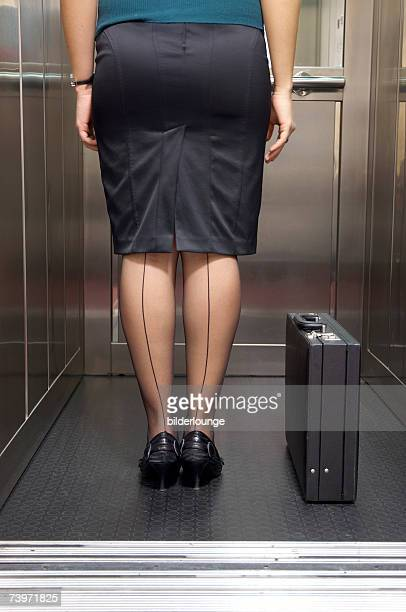 rear view of businesswoman with seamed stockings standing in elevator - seamed stockings stock photos and pictures