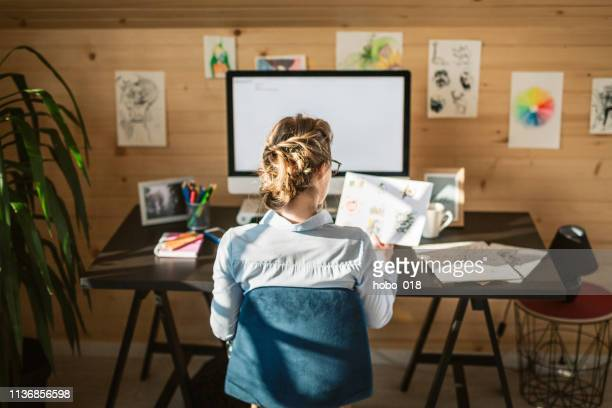 rear view of businesswoman working in creative office - illustrator stock photos and pictures