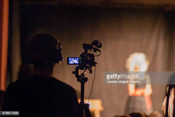 rear view of camera operator at stage theater - cameraman stock photos and pictures
