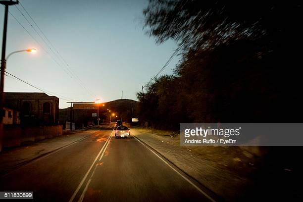 rear view of car on road - andres ruffo stock photos and pictures