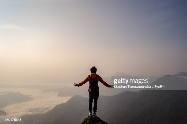rear view of carefree backpacker with arms outstretched looking at landscape while standing on mountain during foggy weather - at the edge of stock pictures, royalty-free photos & images